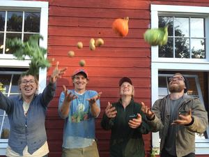 Four people playfully throwing vegetables into the air