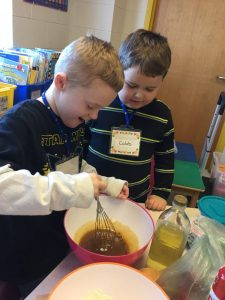 Two boys whisking ingredients in a bowl